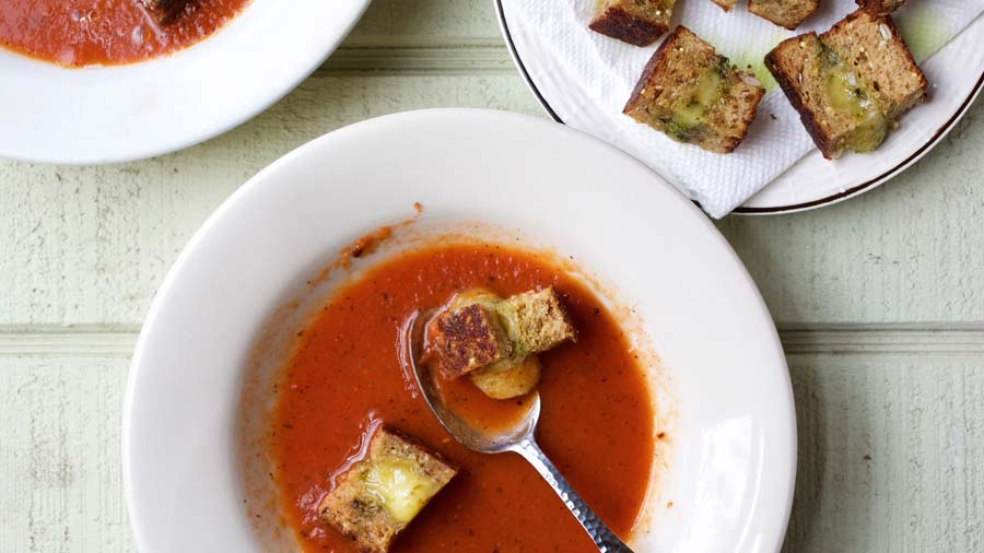 A sophisticated version of a childhood favorite: This delicious but decidedly non-creamy tomato soup has buttery, cheesy bites of grilled cheese sandwich floating atop